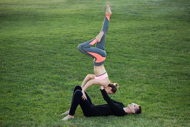 Le couple pratique l'acro yoga dans le parc sur l'herbe