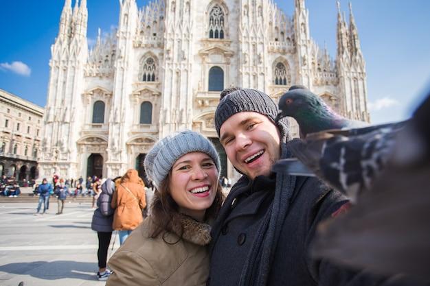 Couple prenant un autoportrait avec un pigeon sur la place du duomo à milan. voyage d'hiver, italie et concept de relation