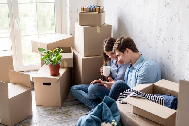 Couple prenant un café tout en emballant pour déménager