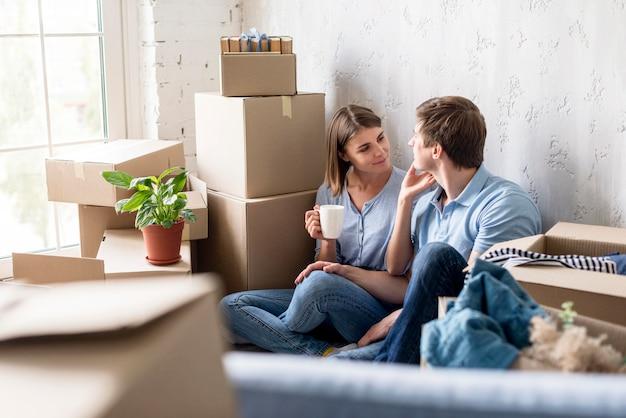 Couple prenant une pause et prenant tout en faisant ses valises pour déménager