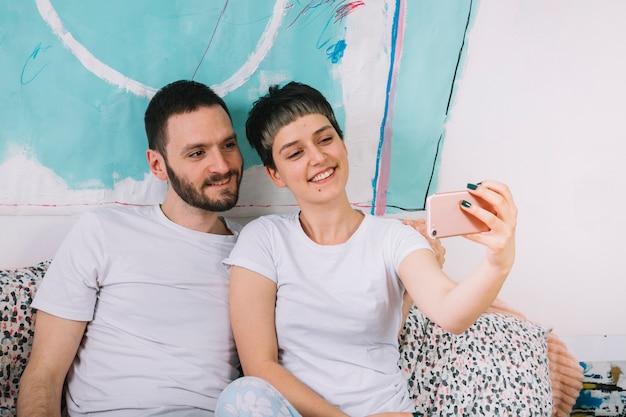 Couple prenant selfie au lit