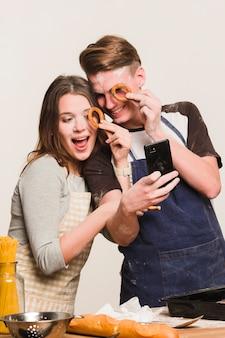 Couple prenant selfie avec des biscuits ronds près des yeux