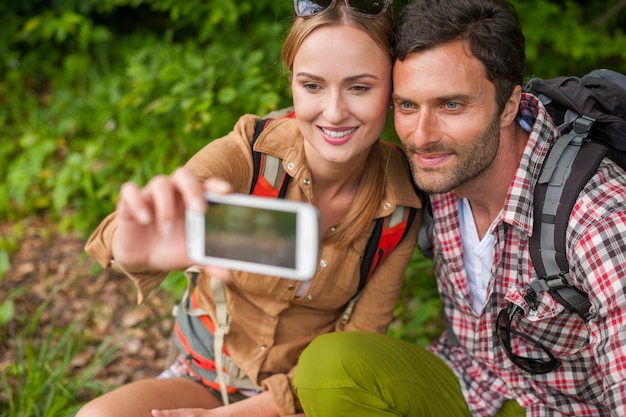 Couple prenant selfie dans la forêt
