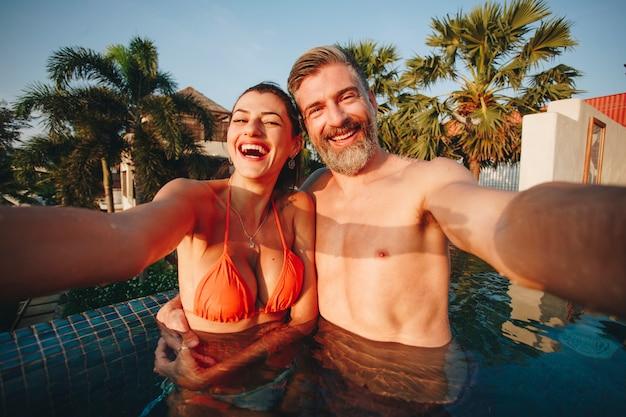 Couple prenant un selfie dans une piscine