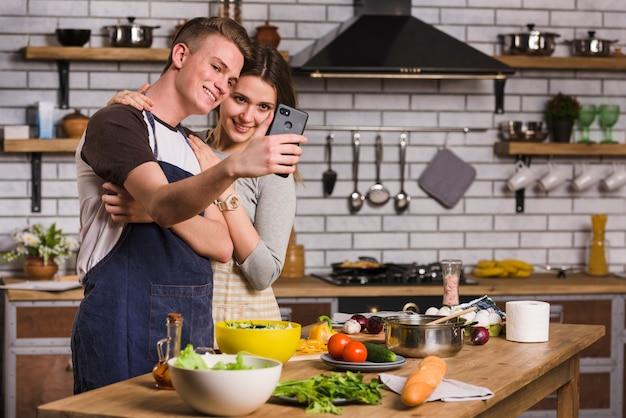 Couple prenant selfie pendant la cuisson des aliments