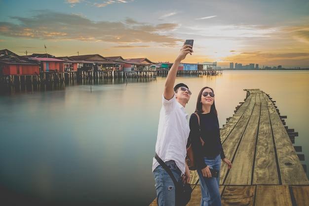 Couple prenant selfie avec téléphone portable au village de pêcheurs de chew jetty au coucher du soleil.