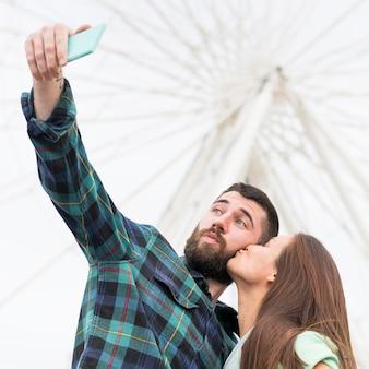 Couple prenant selfie tout en s'embrassant à l'extérieur