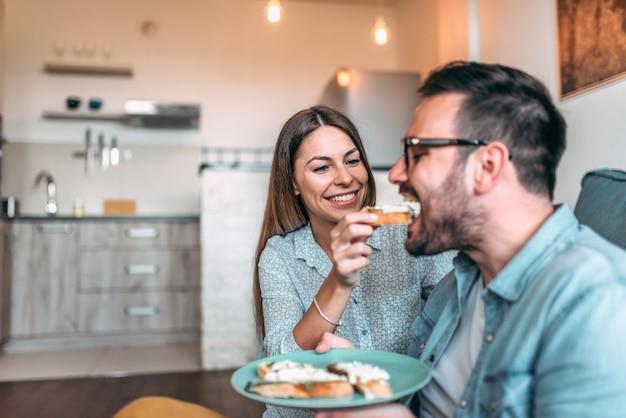 Couple prenant son petit déjeuner ensemble. fille nourrir son petit ami à la maison.