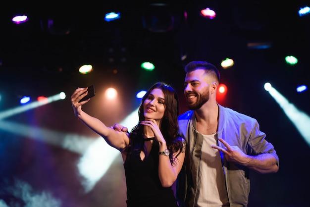Couple prend un selfie avec un téléphone portable lors de la fête de nuit