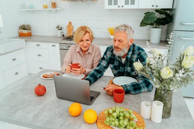 Un couple prend son petit-déjeuner à la maison et regarde quelque chose depuis un ordinateur portable