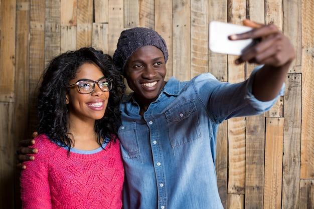 Couple, prendre, selfie, depuis, téléphone portable, contre, mur bois