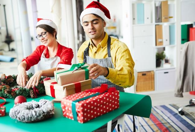 Couple préparant la décoration de noël et les cadeaux d'emballage