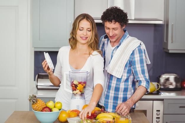 Couple préparant un jus de fruit