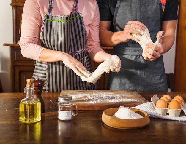 Couple prépare la pâte avec des ingrédients sur une surface en bois