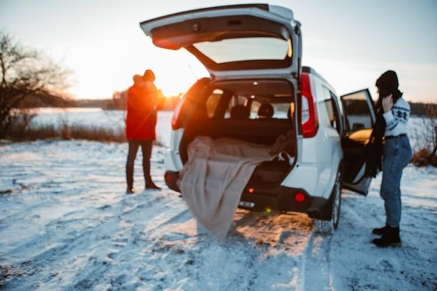 Couple près de la voiture au coucher du soleil d'hiver copie espace flou
