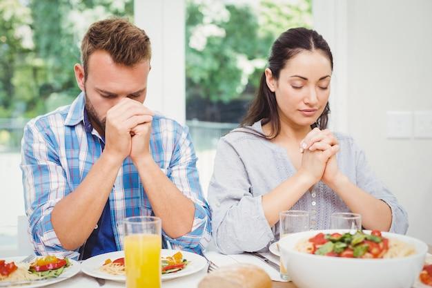 Couple priant à la table à manger
