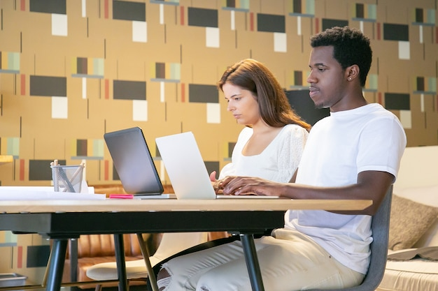 Couple de professionnels de la création assis ensemble à table avec des plans et travaillant sur un projet