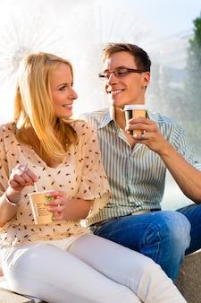 Couple profitant d'un café à emporter pendant une pause