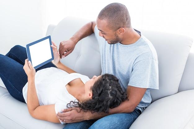 Couple profitant d'un ordinateur portable pour se détendre sur le canapé à la maison