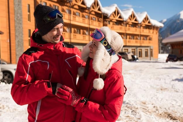 Couple profitant de la vue de chalets et chalets dans une station de ski