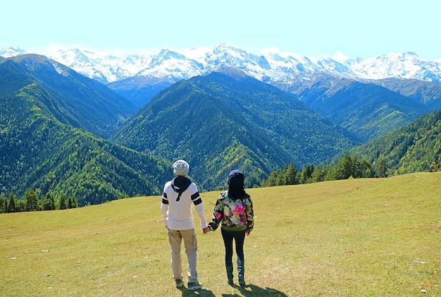 Couple profitez de la vue imprenable sur les chaînes de montagnes du caucase, mestia, région de svaneti, géorgie