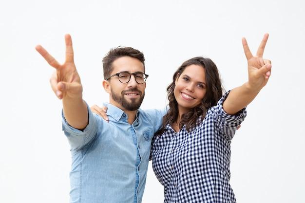 Couple, projection, signe victoire, et, sourire, appareil-photo