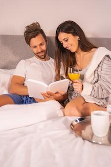 Un couple en pyjama lisant un livre au petit déjeuner de café et de jus d'orange dans le lit de l'hôtel, mode de vie d'un couple amoureux. photo verticale
