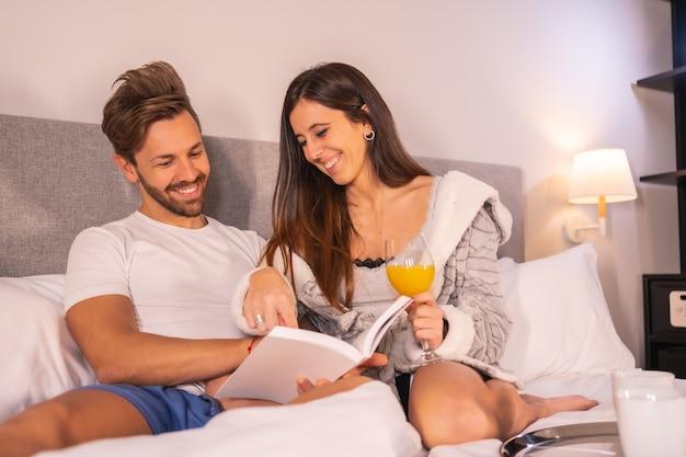 Un couple en pyjama lisant un livre au petit déjeuner de café et de jus d'orange dans le lit de l'hôtel, mode de vie d'un couple amoureux.