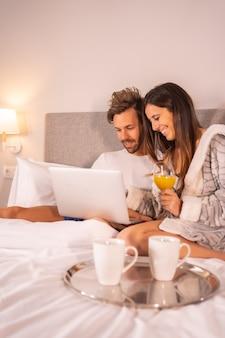 Un couple en pyjama regardant l'ordinateur au petit déjeuner de café et de jus d'orange dans le lit de l'hôtel, mode de vie d'un couple amoureux.
