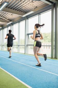 Couple qui court sur la piste intérieure