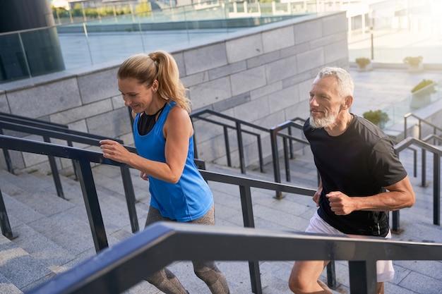 Couple qui monte les escaliers en ville tout en faisant de l'exercice ensemble en plein air sport actif fitness