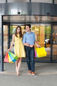 Couple quittant le centre commercial après un shopping réussi
