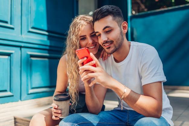 Couple de race mixte amoureux à pied dans la ville. homme arabe et femme buvant du café et utilisant un smartphone