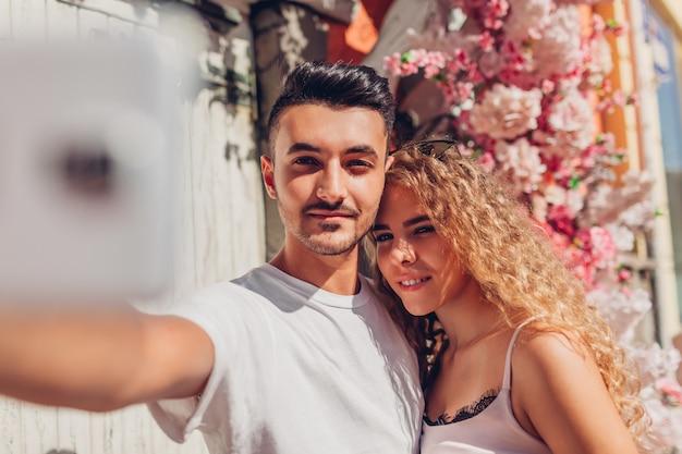 Couple de race mixte amoureux prenant selfie sur smartphone marchant en ville. heureux homme arabe et femme blanche à un rendez-vous romantique