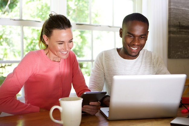 Couple de race mixte utilisant la technologie sans fil à la maison