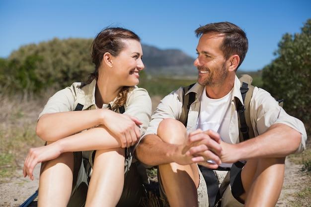 Couple de randonnée prenant une pause sur un terrain de campagne