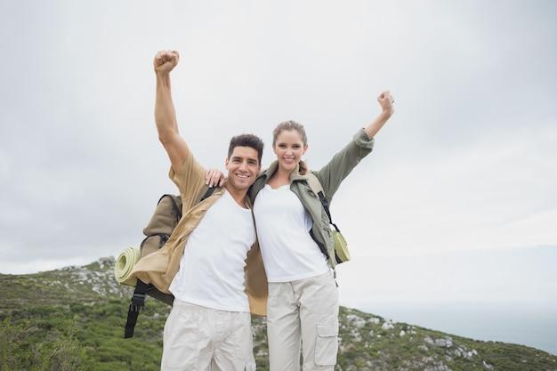 Couple de randonnée qui s'étend de mains sur un terrain de montagne