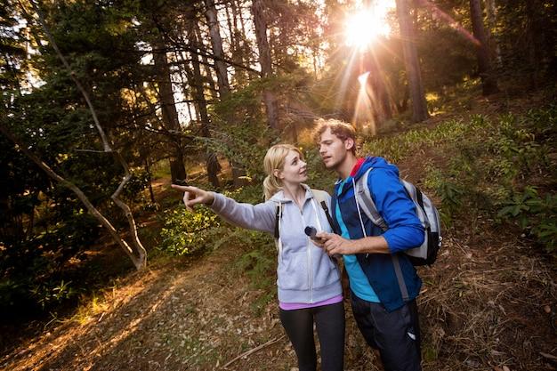 Couple de randonnée tenant une boussole et pointant vers l'avant