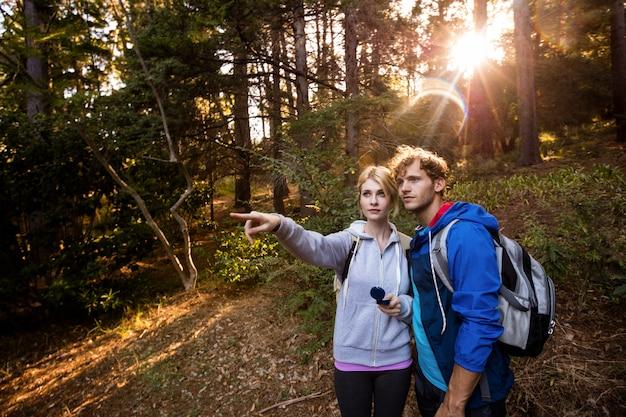 Couple de randonnée tenant une boussole et pointant