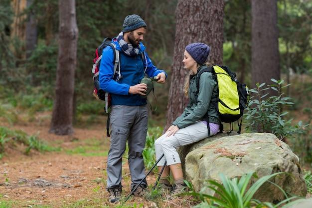 Couple de randonneurs interagissant les uns avec les autres dans la forêt