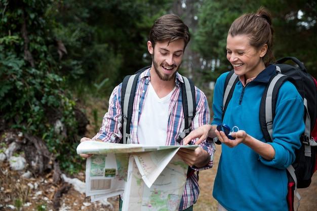 Couple de randonneurs en regardant la carte et la boussole