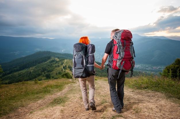 Couple de randonneurs avec sacs à dos sur la route en montagne