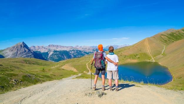 Couple, randonneurs, sommet, montagne, regarder, bleu, lac, sommets