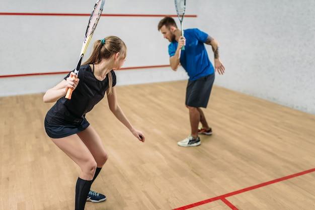 Couple avec raquettes de squash, club d'entraînement en salle