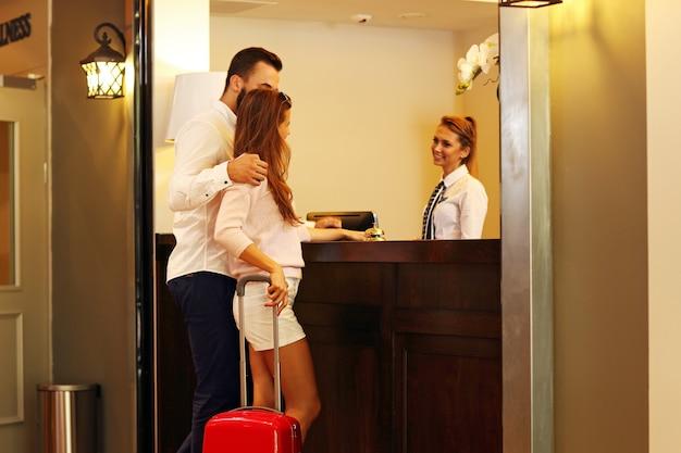 Couple et réceptionniste au comptoir de l'hôtel
