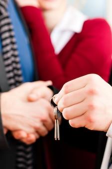 Couple recevant les clés d'un courtier immobilier