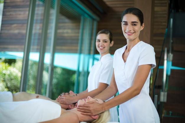 Couple recevant un massage du visage d'un masseur