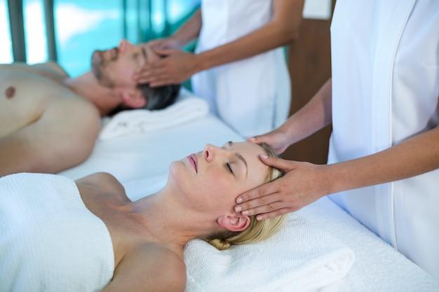 Couple recevant un massage de la tête d'un masseur