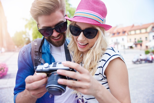 Couple à la recherche sur l'écran de l'appareil photo avec des photos
