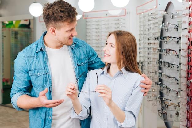 Couple à la recherche de nouvelles lunettes chez l'optométriste